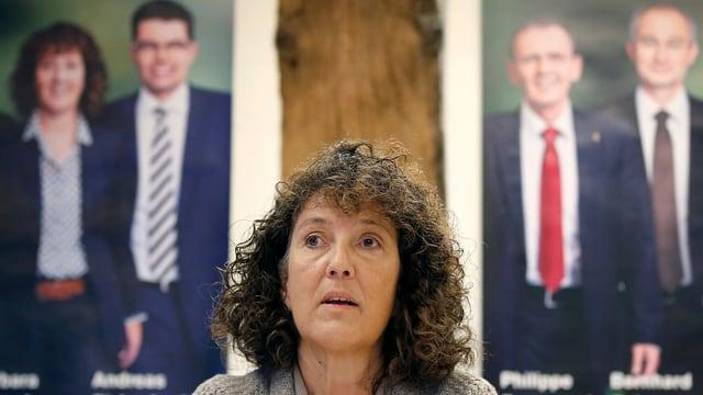 Porträt von Barbara Egger vor den Wahlplakaten.