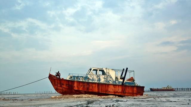 Ein verrostetes Schiff auf dem Trockenen.