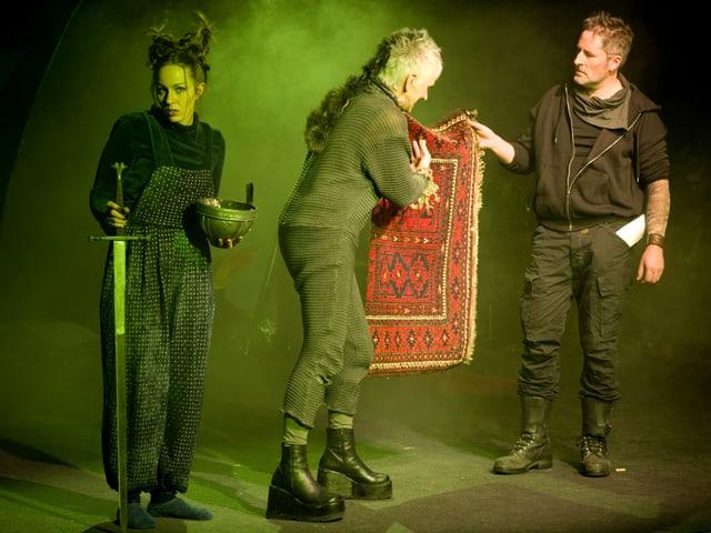 Drei Schauspiele auf einer Bühne. Sie halten ein Schwert und einen Teppich in den Händen