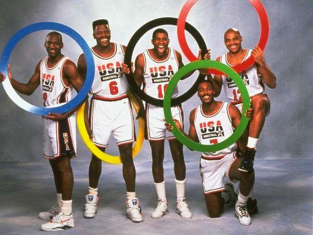 Michael Jordan, Patrick Ewing, Magic Johnson, Karl Malone und Charles Barkley posieren 1992 mit den Olympischen Ringen.