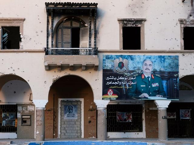 Gebäude mit Schusslöchern und ein Plakat mit Haftar