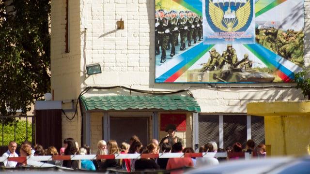 Menschen protestieren vor einem russischen Militärgebäude