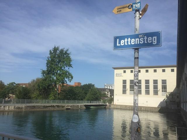 """Blick auf das Elektriztitäswerk Letten - im Vordergrund das Strassenschild """"Lettensteig""""."""