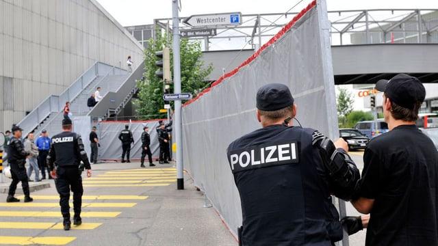Polizisten stellen ein Absperrnetz auf.