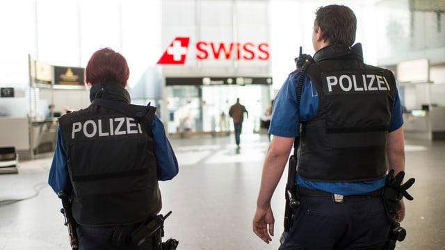 """Zwei Polizisten von hinten fotografiert patrouillieren in einer Halle am Flughafen Zürich, zwischen ihnen im Hintergrund der Schriftzug """"Siwss"""""""