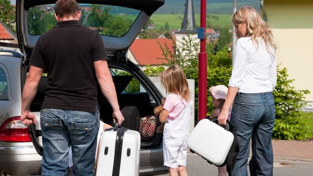 Offener Kofferraum beim Auto, Familie mit Koffern am Einladen