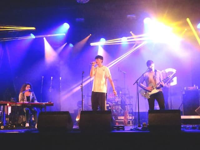 Bühne mit Musikerin und zwei Musikern.