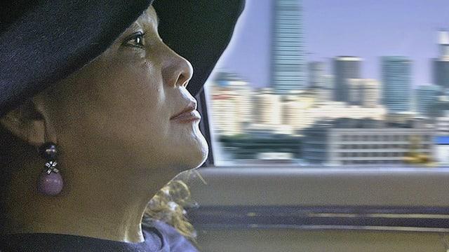 Chinesische Unternehmerin im Auto im Hintergrund eine Skyline