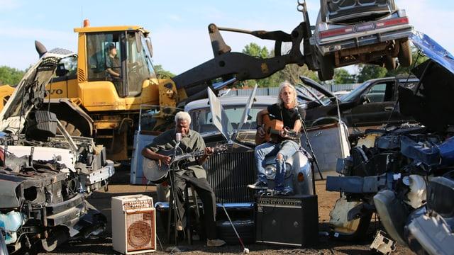 Zwei Musiker speilen vor einem Schrottplatz.