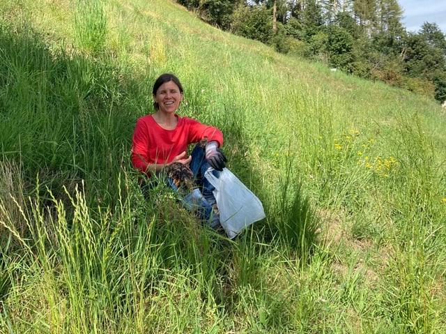 Flurina Manetsch sitzt in einer Blumenwiese. In der Hand hält sie einen Plastiksack und trägt Handschuhe.