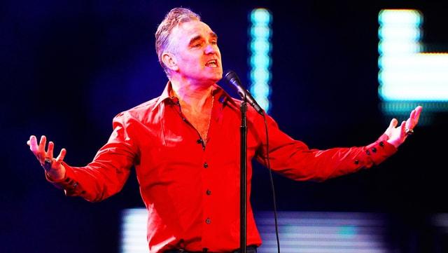 Morrissey, singend mit ausgebreiteten Armen, im knallroten Hemd