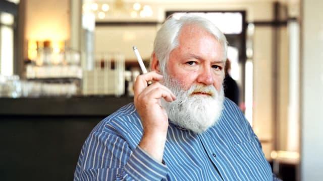 Werner Morlang, an einem Tisch sitzend, vor sich eine Tasse Kaffee, Zigarette rauchend.