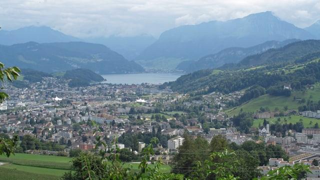 Blick von oben auf Siedlungsgebiet mit See und Bergen im Hintergrund.