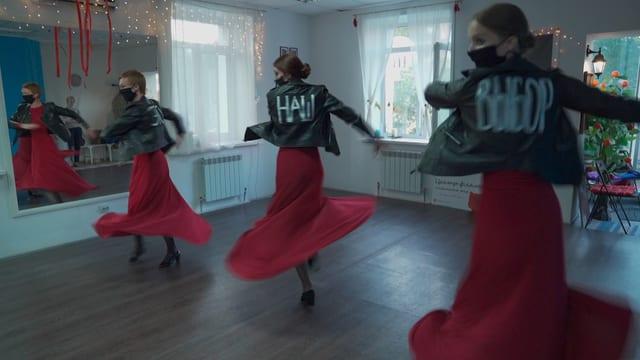 Drei Frauen tanzen Flamenco in Jeansjacken.