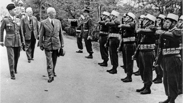 Mann in Anzug schreitet eine militärische Formation ab.