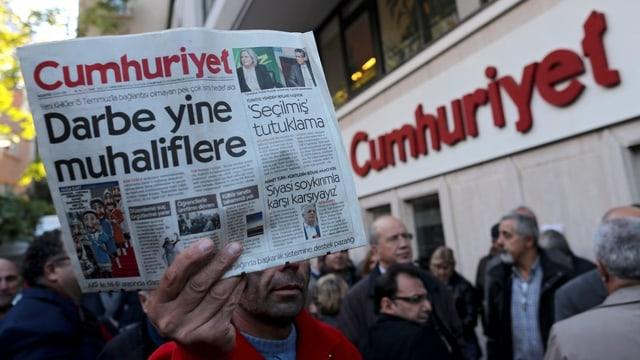 Eine Person hält eine Zeitungsexemplar vor der Redaktion der «Cumhuriyet» in der Hand.