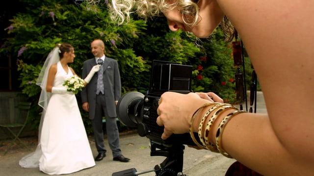 Eine Fotografin lichtet ein Hochzeitspaar ab