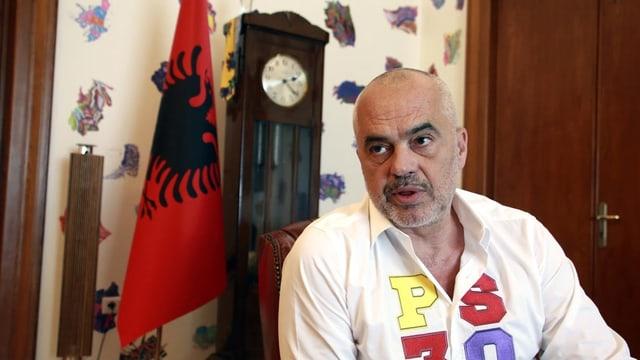 Mann vor albanischer Flagge.