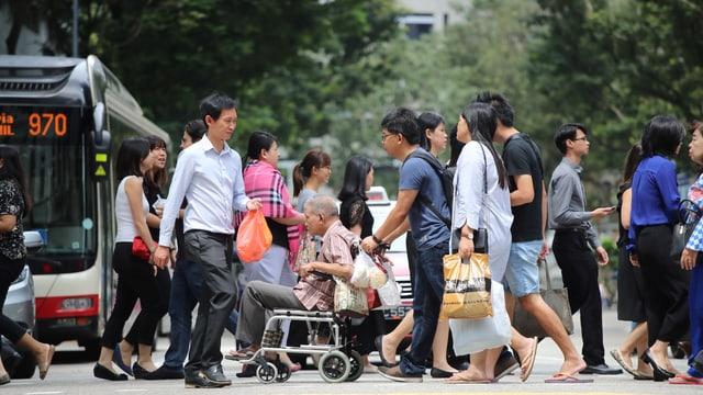 Menschen überqueren in Singapur eine Strasse.