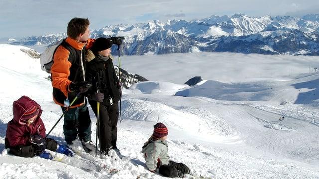Familie beim Skifahren mit Blick auf Innerschweizer Alpenkette.