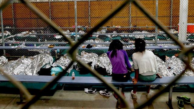 Blick durch einen Zaun auf zwei Mädchen, die in einem Lager auf einen Fernseher schauen
