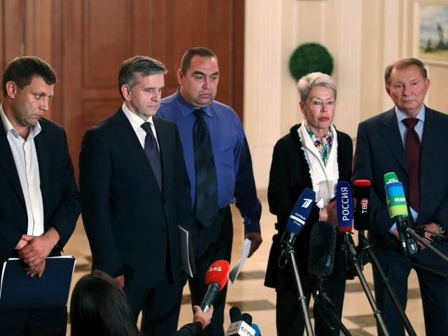 Vier Männer und eine Frau stehen nebeneinander vor Mikrofonen.