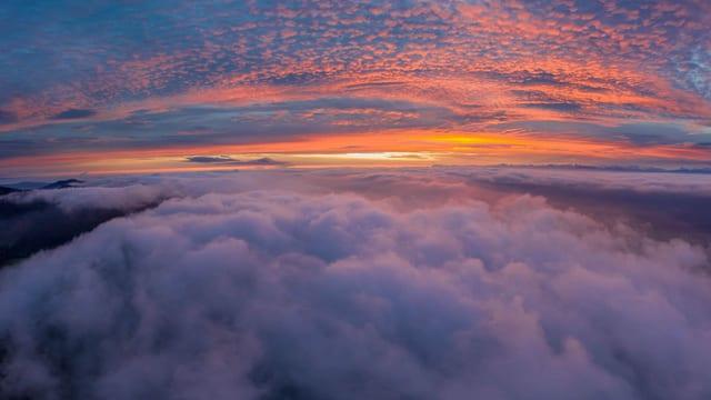 Drohnenaufnahme: Oben Wolkenfelder und Morgenrot, unten aufgelockerter Nebel.
