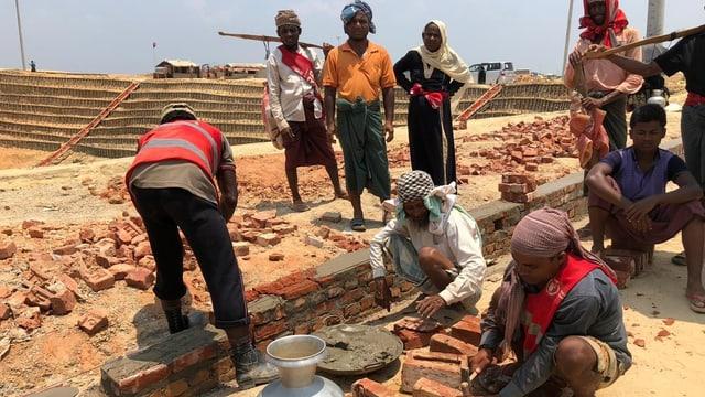 Handwerker in einem Flüchtlingslager beim Häuser bauen.