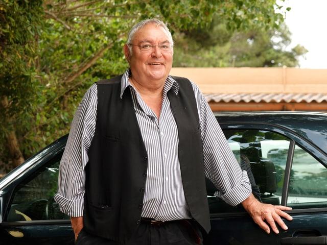 Porträt von Mathias Gnädinger vor seinem Auto.