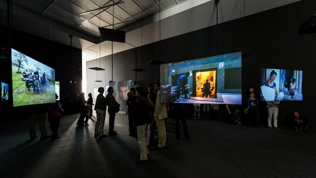 Menschen stehen vor Filmleinwänden in einem Ausstellungsraum.