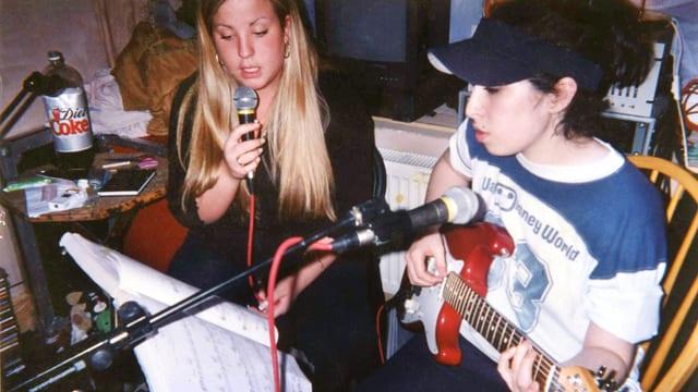 DIe junge Amy Winehouse mit Freundin am Gitarre spielen.