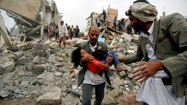 Ein Mann trägt ein kleines Mädchen auf den Armen. Im Hintergrund Trümmer nach einem Luftanschlag.