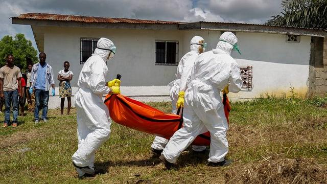 Drei Personen in weissen Anzügen tragen einen orangen Leichensack weg, im Hintergrund eine weisse Hütte und einige Zuschauer.