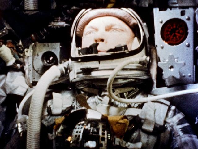 John Glenn sitzt im Raumanzug in einer Raumkapsel
