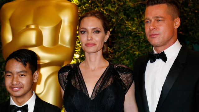 Drei Personen in Abendrobe vor einem Oscar