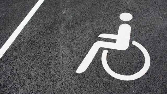 Ein Behinderten-Zeichen auf einer schwarzen Strasse.