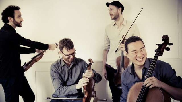Die vier Streicher des Quartetts nebeneinander. Sie sind alle an ihren Instrumenten und scheinen glücklich.