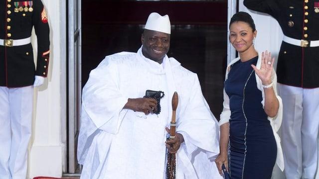 Yahya Jammeh sitzt, daneben steht eine frau