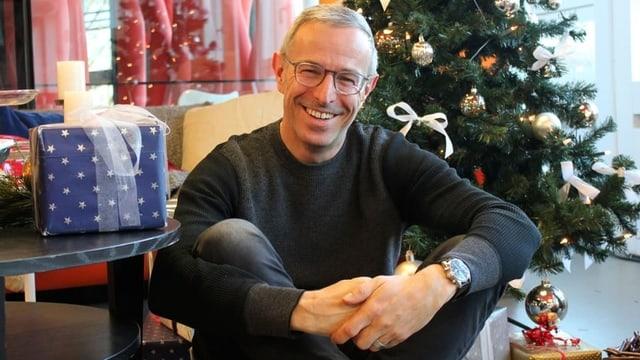 Moderator Dani Fohrler sitzt vor einem Weihnachtsbaum.
