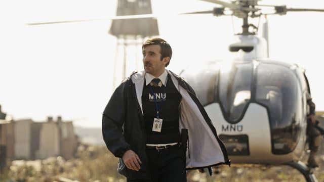 Ein Mann in Polizeimontur steht vor einem Helikopter.