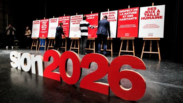 Plakate für Sion 2026 werden auf einer Bühne aufgestellt.