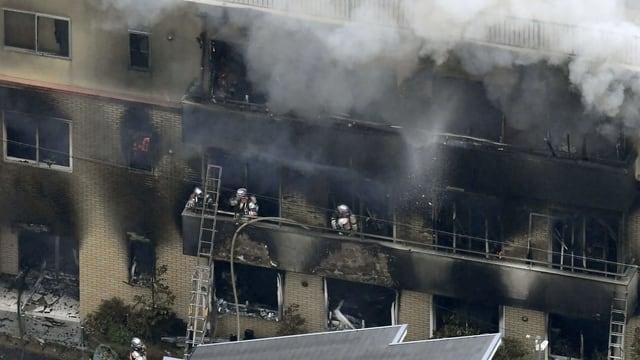 Purtret da la chasa a Tokio che arda. I vegn bler fim or da las fanestras e pumpiers èn vid stizzar.