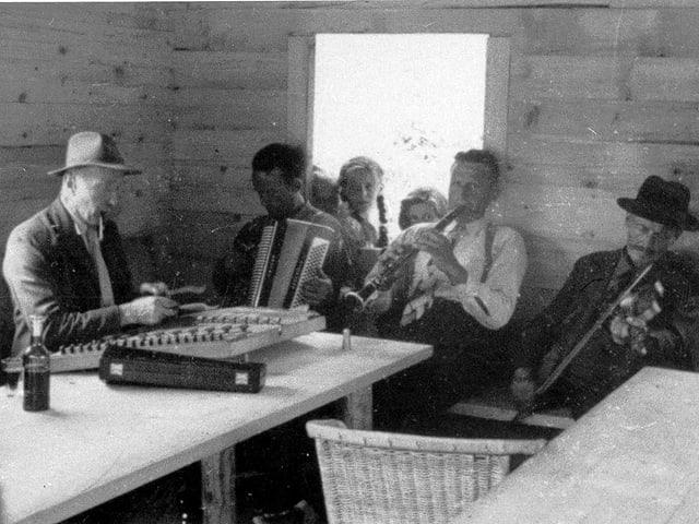 Vier Männer spielen Hackbrett, Klarinette, Harmonika und Geige.
