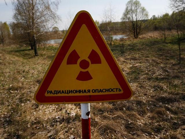 Warnschild Atomstrahlung, dahinter eine karge Landschaft