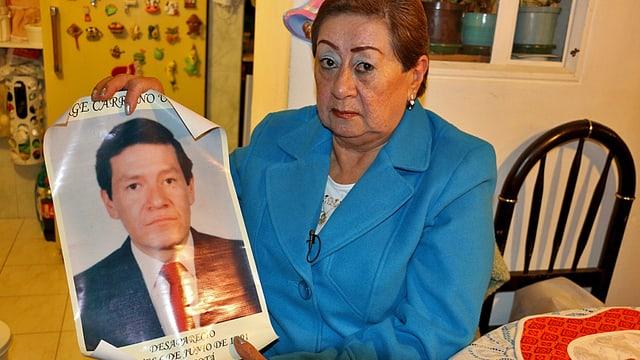 Eine Frau hält ein Plakat mit dem Porträt ihres Bruders hoch.