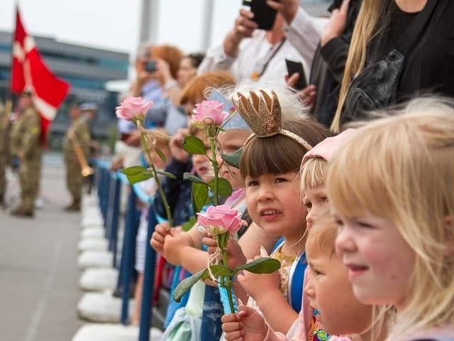 Mädchen stehen an einer Strasse mit Rosen in den Händen. Eines hat eine Krone an.