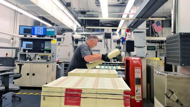 Ein Mann stapelt Bögen auf denen Dollarnoten gedruckt sind.