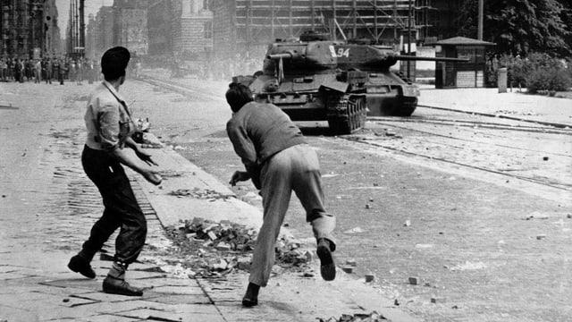 Zwei Männer werfen Steine auf einen sowjetischen Panzer. Schwarz-Weiss-Fotografie