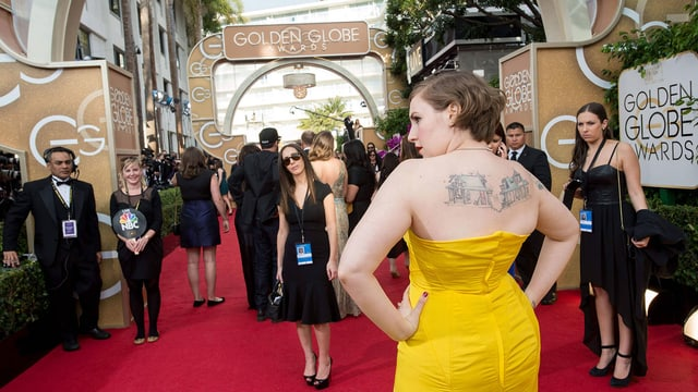 Eine Frau in einem gelben Kleid auf dem roten Teppich der Golden Globes.