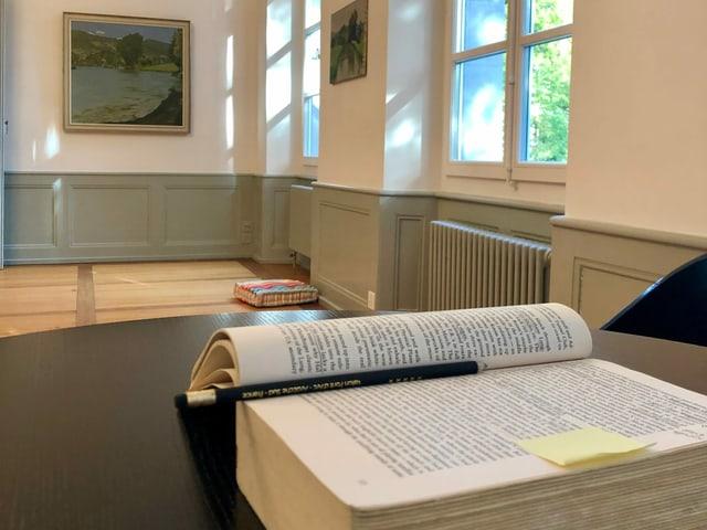 aufgeschlagenes Buch auf einem Tisch in einem Ausstellungsraum